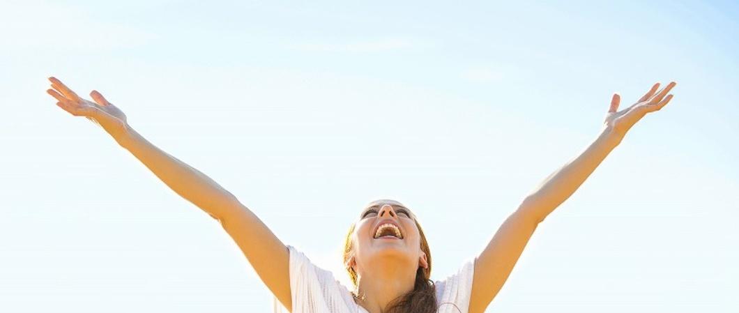 笑顔で天に向かって両手を広げ仰ぐ外国女性