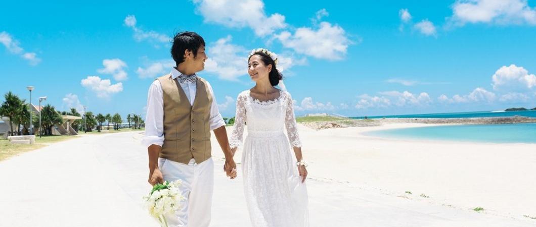 タキシードとドレスで浜辺を歩く夫婦
