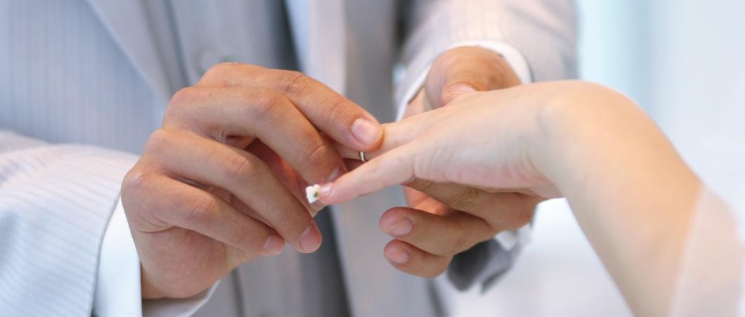 女性に結婚指輪をはめる男性