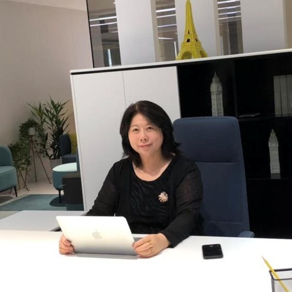 デスクに座りパソコンを持って微笑む女性
